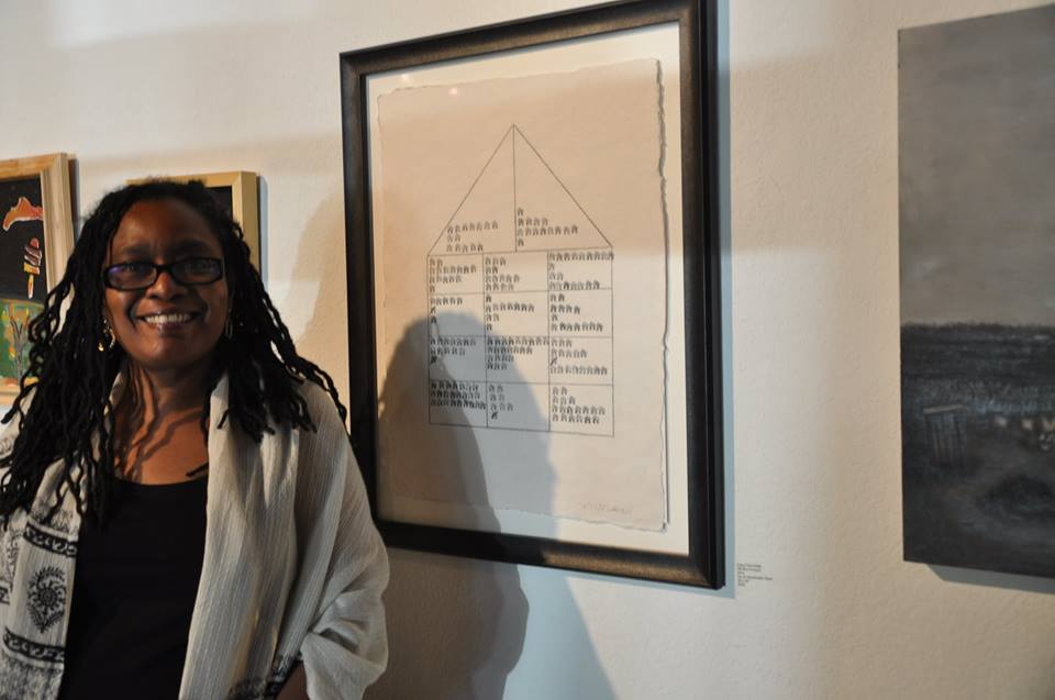 "Artist Cheryl Derricotte  at the OCCCA opening with her artwork ""We Buy Houses,""  handmade paper, ink (2013"
