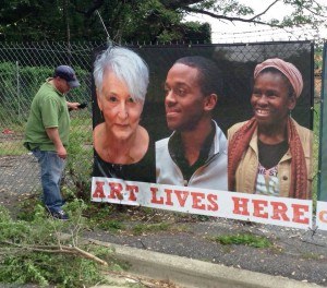 "Glass artist Diane Cabe's image overlooks the installation of the ""Art Lives Here"" fence wrap."
