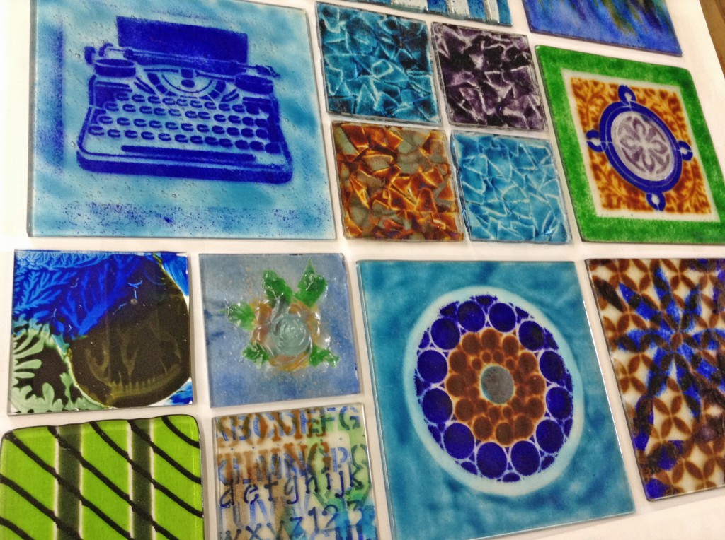The first batch of fused glass artworks is reviewed in the studio.