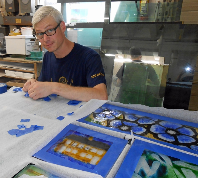 Josh Hershman preps the glass prior to mounting into the powdercoated steel sculpture structure.