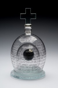 "Tim Tate; ""Two Paths Taken"" ;Blown Glass, Found Objects, Original Text; 18""x10""x10""; 2004. Said Tim: ""On the inner dome is the etched story of how my life changed after becoming HIV+. On the outer dome is my fantasy of what my life would have been like if things had been different. Both lives have their pros and cons. What I lost in one narrative I gained even more back in the second. The magic 8 ball in the center references the role that chance played in my life."""