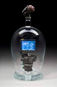 "Tim Tate; ""A Century Of Longing""; Blown & Cast Glass / electronics, original video; 16"" x 7"" x 7""; 2005. photo by Pete Duvall.  The top finial is of a cast glass hand holding a Victorian bouquet. Inside there is a film projector and a stack of film. The video is an 1896 sound test by Edison. In it, two men dance for the first time in film history. A century has passed, and not only has the definitions of ""New Media"" changed (it begins with Edison's films), but the way we perceive the 2 men dancing has changed as well. Edison was testing whether or not he could sync sound and motion at the time. These men have been dead for 50 years....but they dance on, oblivious that this 3 minutes would be remembered as iconic to a population they couldn't have imagined. It was probably thought of as amusing back then, or convenient......but the way we perceive these 2 men has evolved so much over time that now it seems touching and sweet to think of them dancing for eternity together."