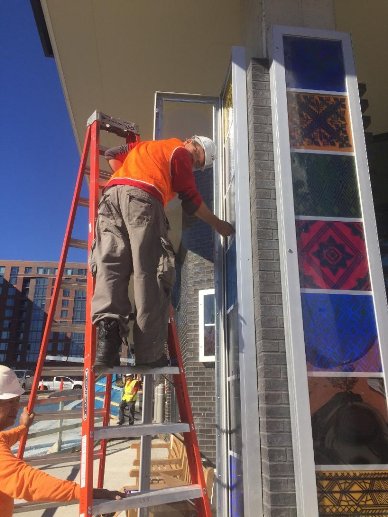 WGS Co-Director Erwin Timmers sets the final glass artwork panels in the corner column at the 900 Thayer site.